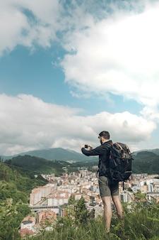 Jonge man die een foto van het landschap met de smartphone