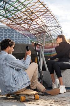 Jonge man die een foto van zijn vriend naast een scooter neemt