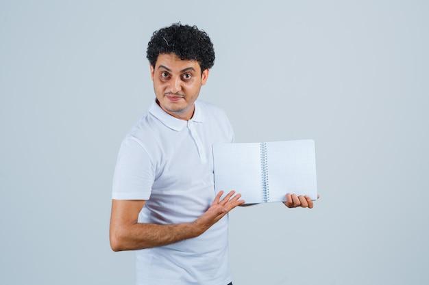 Jonge man die een geopend notitieboekje in een wit t-shirt en een spijkerbroek toont en er serieus uitziet, vooraanzicht.