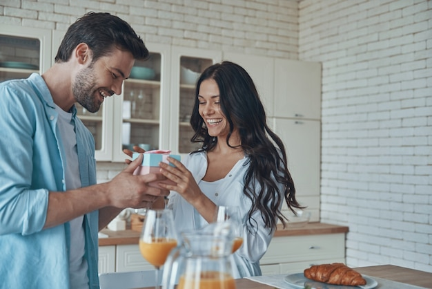 Jonge man die een geschenkdoos geeft aan zijn vriendin tijdens het ontbijt in de huiselijke keuken