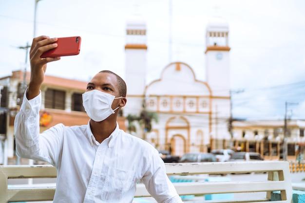 Jonge man die een gezichtsmasker draagt en een selfie maakt met een moskee