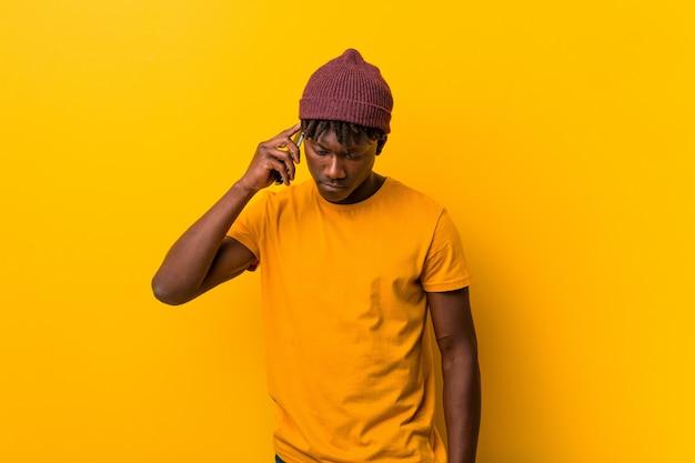 Jonge man die een hoed draagt en een telefoon gebruikt