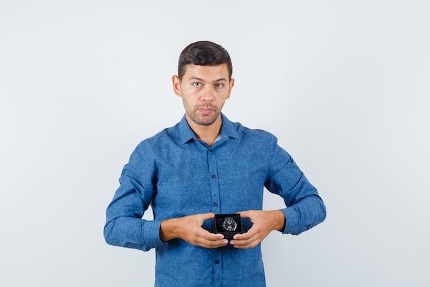 Jonge man die een horlogedoos in een blauw shirt vasthoudt en er verstandig uitziet, vooraanzicht.