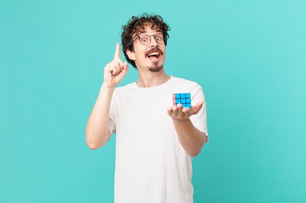Jonge man die een intelligentieprobleem oplost en zich een gelukkig en opgewonden genie voelt nadat hij een idee heeft gerealiseerd