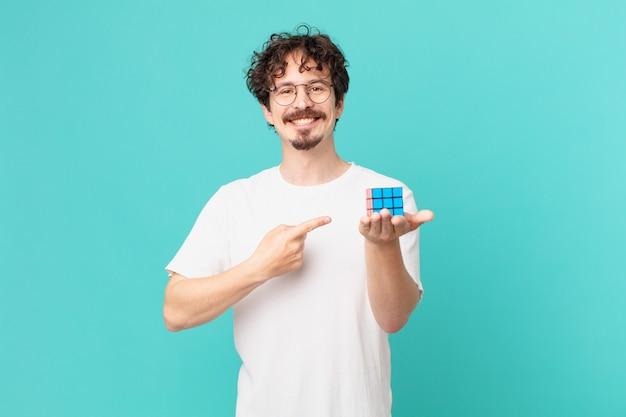 Jonge man die een intelligentieprobleem oplost, vrolijk glimlacht, zich gelukkig voelt en naar de zijkant wijst