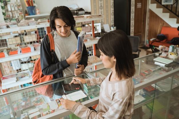 Jonge man die een kantoorboekhandel bezoekt, praat met de kassier van het meisje over prijzen
