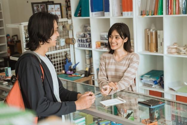 Jonge man die een kantoorboekhandel bezoekt, praat met de vrouwelijke kassamedewerker