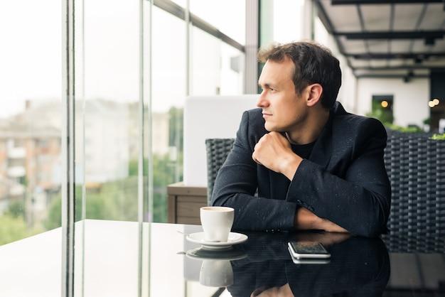 Jonge man die een kopje koffie drinkt in het café