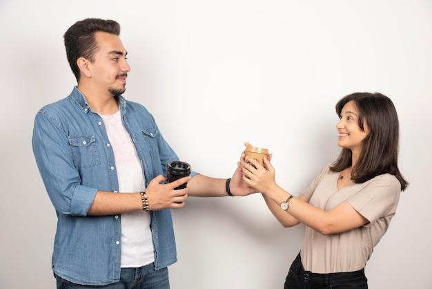 Jonge man die een kopje koffie geeft aan de glimlachende vrouw.