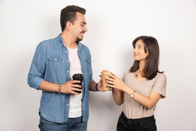 Jonge man die een kopje koffie geeft aan de jonge vrouw.