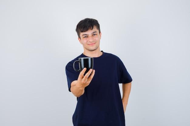 Jonge man die een kopje koffie in zwart t-shirt aanbiedt en zacht kijkt. vooraanzicht.