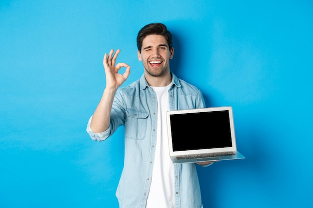 Jonge man die een laptopscherm en een goed teken toont, een promo op internet goedkeurt of leuk vindt, tevreden glimlacht, over een blauwe achtergrond staat
