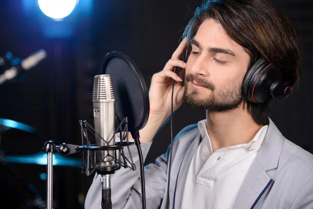 Jonge man die een lied in een professionele studio opneemt.