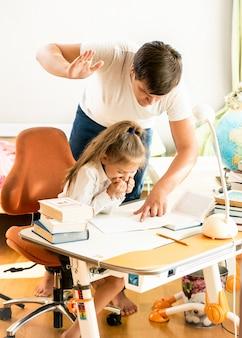 Jonge man die een manchet in de nek geeft aan dochter die huiswerk maakt