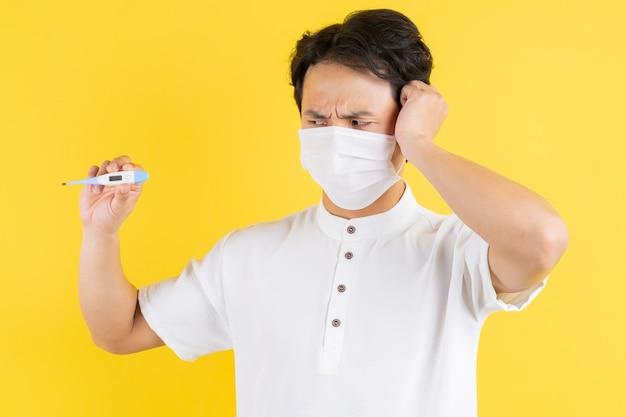 Jonge man die een masker draagt, een thermometer vasthoudt en hoofdpijn voelt