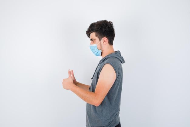 Jonge man die een masker draagt terwijl hij zijn duimen in een grijs t-shirt laat zien en er serieus uitziet