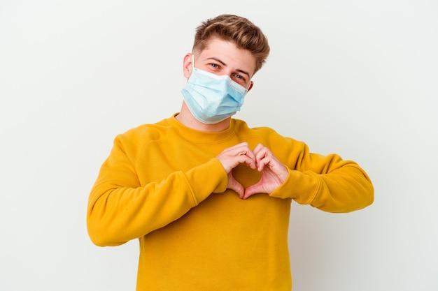 Jonge man die een masker voor coronavirus draagt dat op witte muur wordt geïsoleerd die en een hartvorm met handen glimlacht toont