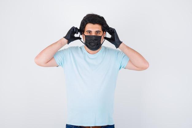 Jonge man die een medisch masker en handschoenen in een t-shirt draagt en er verstandig uitziet. vooraanzicht.