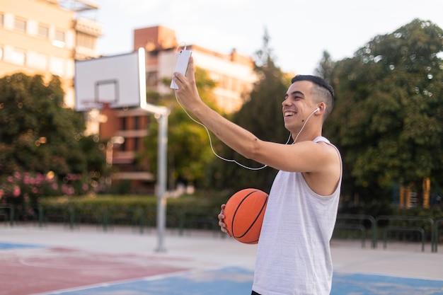 Jonge man die een mobiele telefoon selfie op een basketbalveld