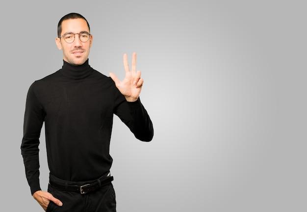 Jonge man die een nummer drie gebaar maakt