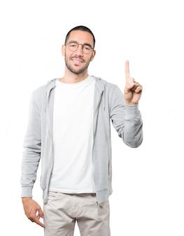 Jonge man die een nummer één gebaar maakt