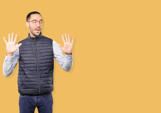 Jonge man die een nummer tien gebaar maakt