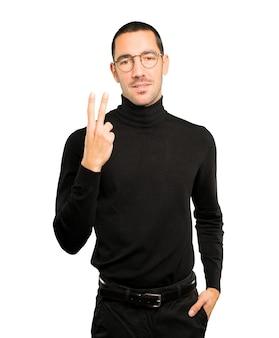 Jonge man die een nummer twee gebaar maakt