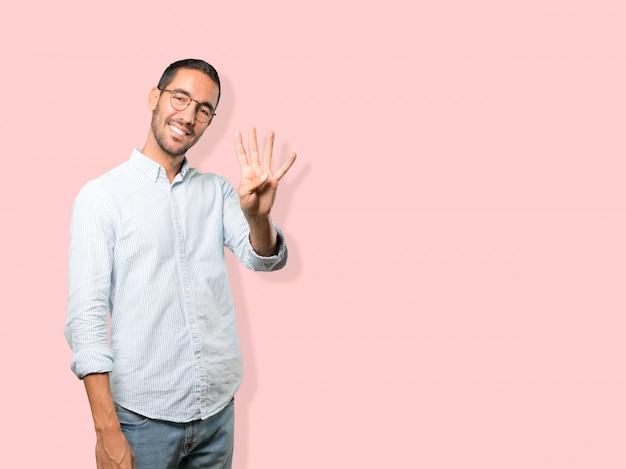Jonge man die een nummer vier gebaar maakt