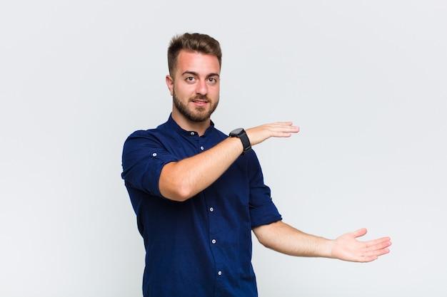 Jonge man die een object met beide handen aan de zijkant van de kopie ruimte vasthoudt, een object toont, aanbiedt of adverteren