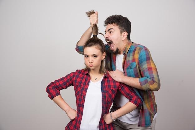 Jonge man die een paardenstaart van een vrouw vasthoudt en tegen haar schreeuwt.