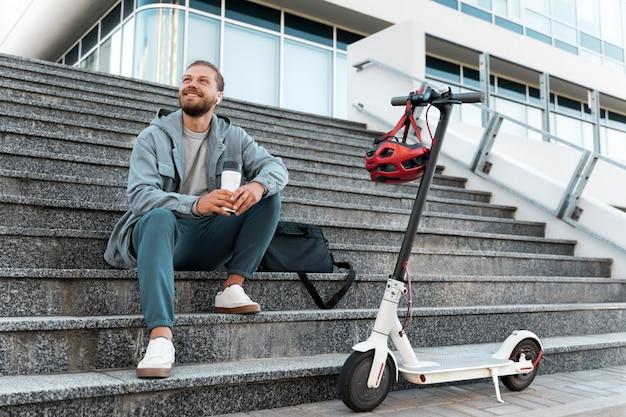 Jonge man die een pauze neemt na het rijden op zijn scooter