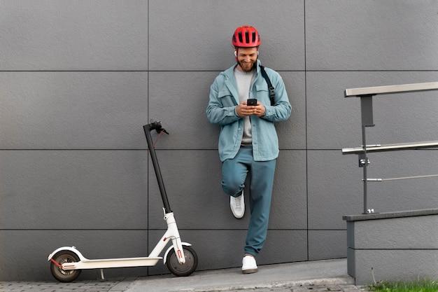 Jonge man die een pauze neemt nadat hij buiten op zijn scooter heeft gereden