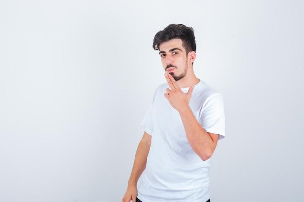 Jonge man die een pistoolgebaar in een t-shirt toont en er zelfverzekerd uitziet