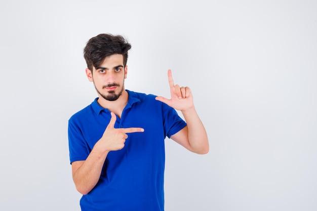 Jonge man die een pistoolgebaar toont en ernaar wijst in een blauw t-shirt en er serieus uitziet