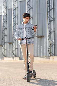 Jonge man die een ritje maakt met een scooter