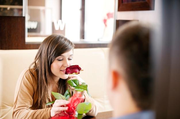 Jonge man die een roos zijn vriendin geeft