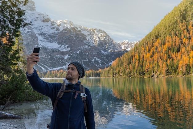 Jonge man die een selfie in de bergen