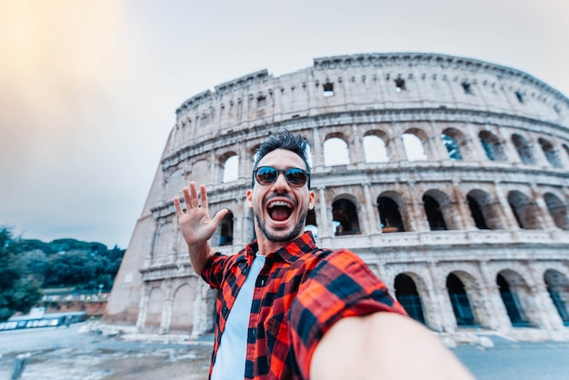 Jonge man die een selfie neemt voor colosseum in rome, italië