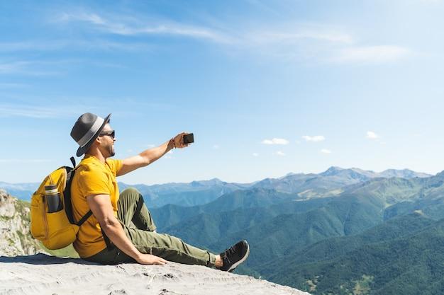 Jonge man die een selfie op de top van de berg neemt.