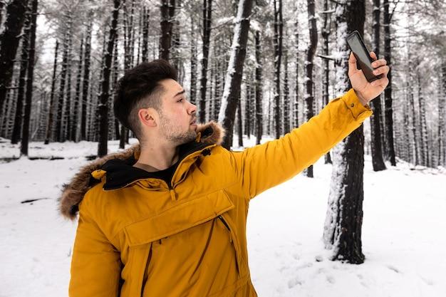 Jonge man die een selfie op een besneeuwd bos met een gele anorak