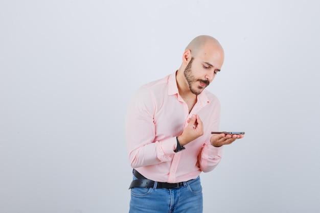 Jonge man die een spraakbericht opneemt op mobiele telefoon