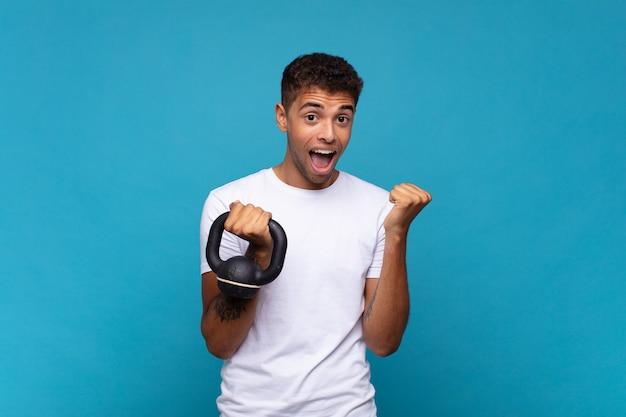 Jonge man die een sumbbell optilt die zich geschokt, opgewonden en gelukkig voelt, lacht en succes viert, zeggend wow!