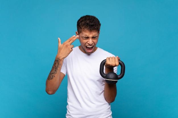 Jonge man die een sumbell optilt die er ongelukkig en gestrest uitziet, zelfmoordgebaar maakt een pistoolteken met de hand, wijzend naar het hoofd