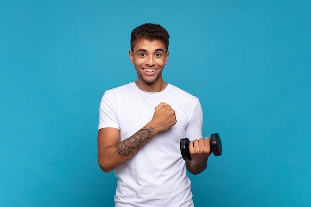 Jonge man die een sumbell optilt, voelt zich gelukkig, positief en succesvol, gemotiveerd wanneer hij voor een uitdaging staat of goede resultaten viert