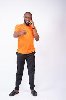 Jonge man die een telefoongesprek voert en duimen omhoog geïsoleerd op een witte muur