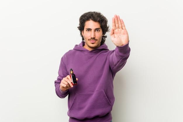 Jonge man die een verdamper houdt die zich met uitgestrekte hand bevindt die stopbord toont, dat u verhindert.