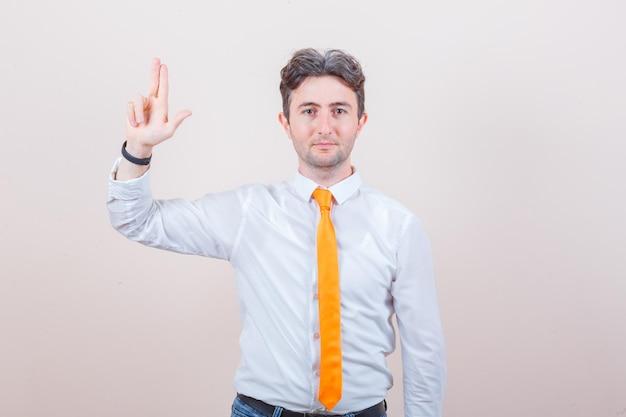 Jonge man die een vingerpistool maakt in een wit overhemd, een stropdas en er zelfverzekerd uitziet