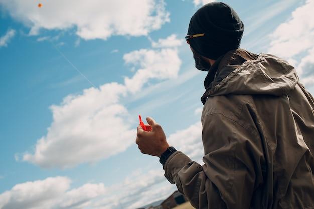 Jonge man die een vlieger vliegt tegen de blauwe lucht