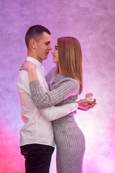 Jonge man die een voorstel met gouden ring met diamant doet aan zijn meisje. valentijns verrassing