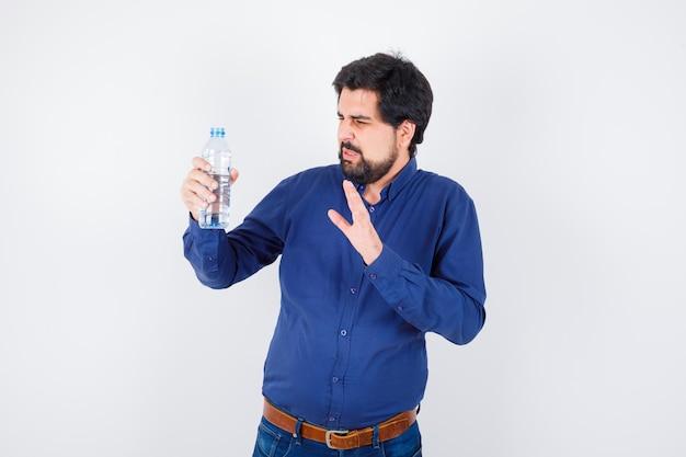 Jonge man die een waterfles vasthoudt en de hand ernaartoe uitstrekt in een blauw shirt en spijkerbroek en er ontevreden uitziet. vooraanzicht.